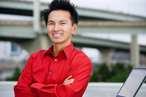 Asian Businessman Portrait Outdoors Crossing Arms, Using Laptop stock photo