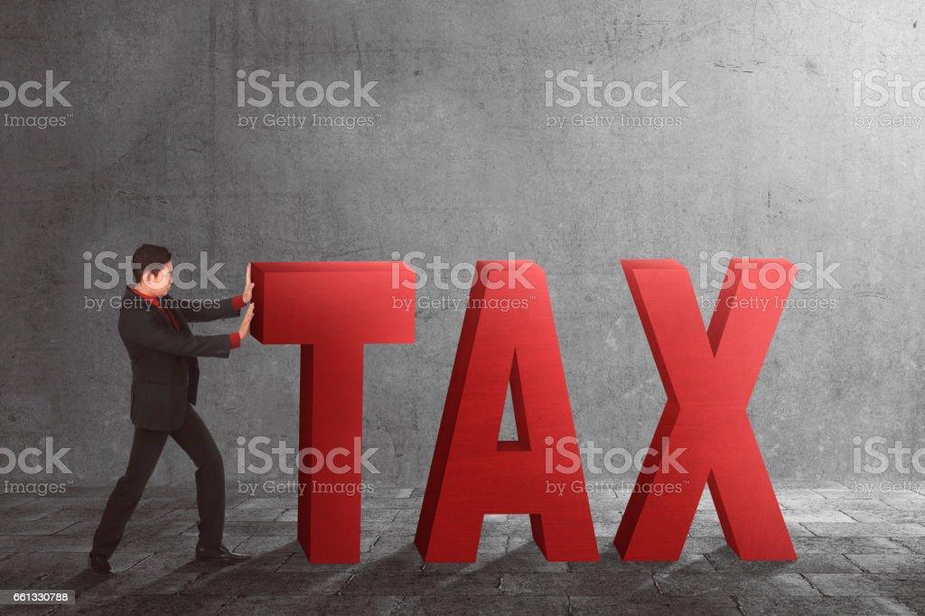 Asian businessman pushing away Tax text stock photo