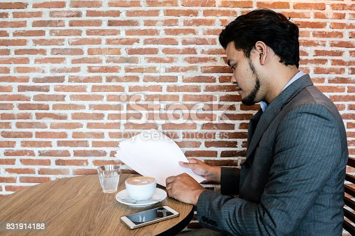 istock Asian businessman reading the document in coffee shop with background is brick wall. 831914188
