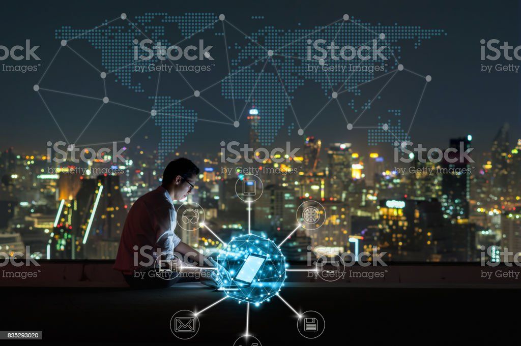 Asian businessman sitting and using the laptop for online shopping with omni channel over the cityscape background at night time, Business success and technology concept stock photo