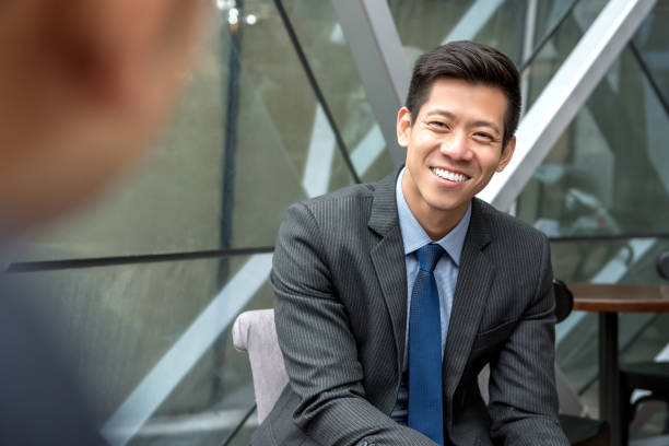 Asian businessman sitting at office lounge Friendly smiling handsome Asian businessman sitting at office lounge talking with his colleague southeast asian ethnicity stock pictures, royalty-free photos & images