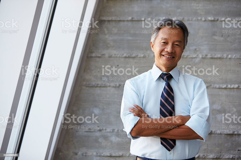 Asian Businessman Standing Against Wall In Modern Office stock photo