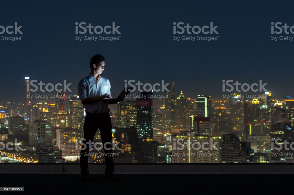 Asian businessman standing and using the laptop over the cityscape background at night time, Business success and technology concept - Royalty-free Adult Stock Photo