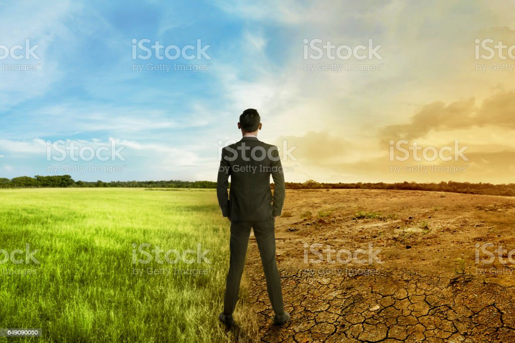 Asian businessman standing between different climate stock photo