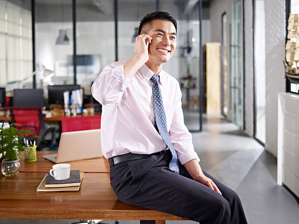 asian businessman talking on cellphone stock photo