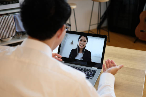 Asian businessman talking to colleague on web meeting Asian businessman talking to colleague on web meeting job interview stock pictures, royalty-free photos & images