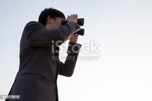 520244535 istock photo Asian businessman using binoculars during sunset being isolated 523478516