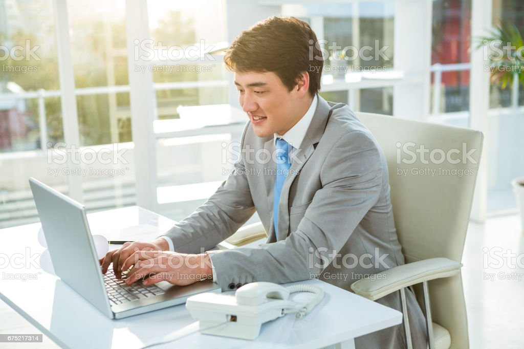 Asian businessman using his computer royalty-free stock photo