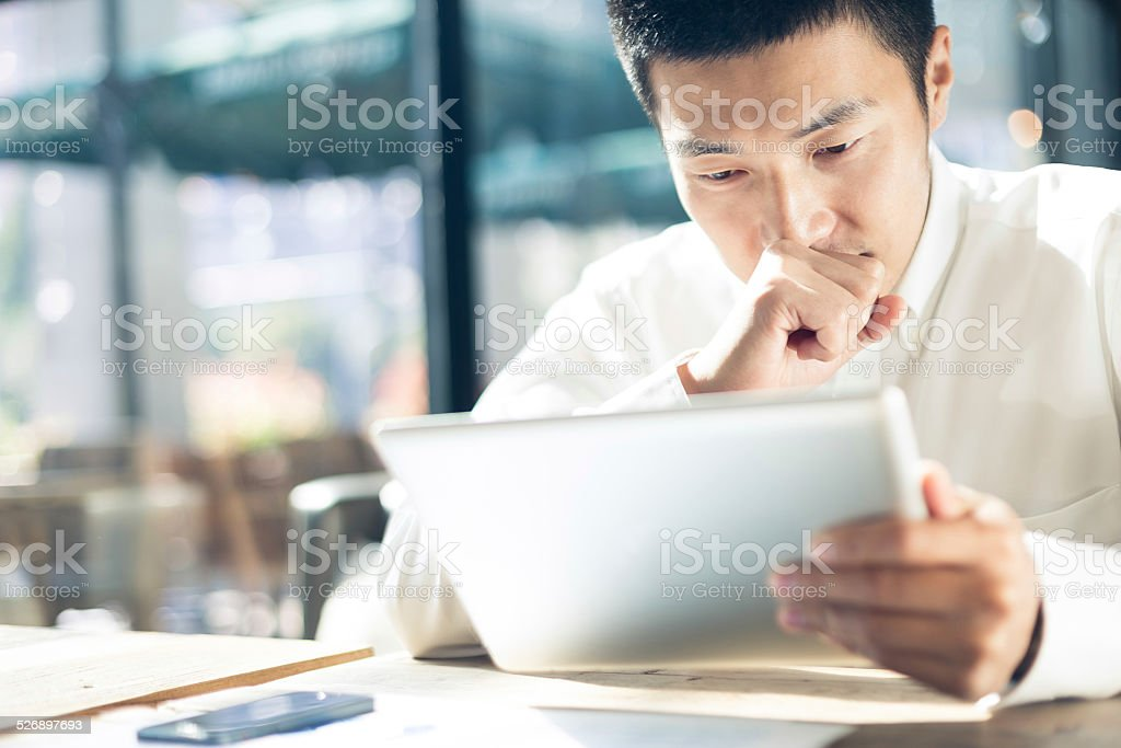 Asian businessman using tablet during break in cafe. stock photo