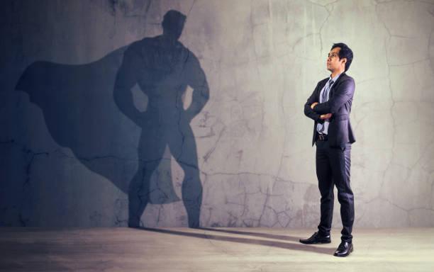 Asiatische Geschäftsmann mit seinem Schatten von Superhelden an der Wand. Konzept der mächtigen Mann – Foto