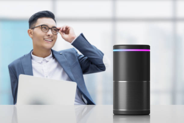 Asian businessman with smart speaker Smiling Asian businessman in glasses sitting in office with laptop and voice controlled smart speaker on the table. Concept of hi tech. smart speaker stock pictures, royalty-free photos & images