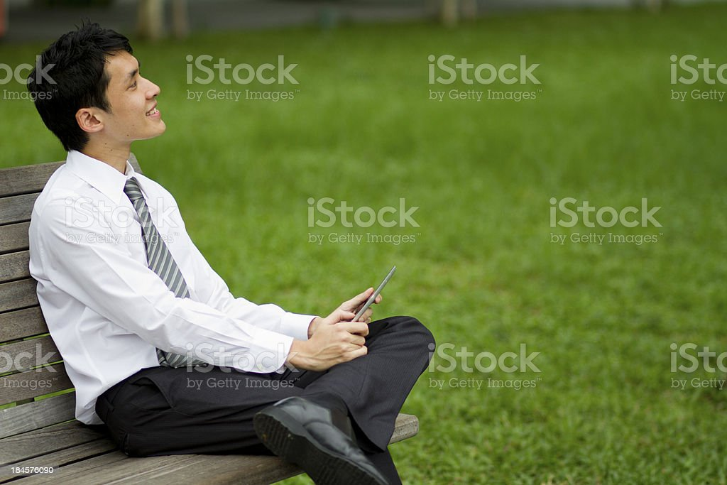 Asian businessman working outdoors with a tablet. royalty-free stock photo