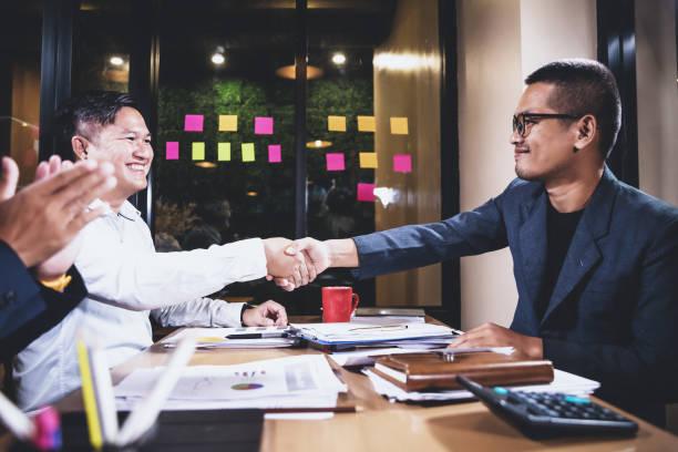 Empresarios asiáticos discutiendo el trabajo sentado en la sala de conferencias de la escena nocturna, análisis gráfico y concepto de trabajo en equipo - foto de stock