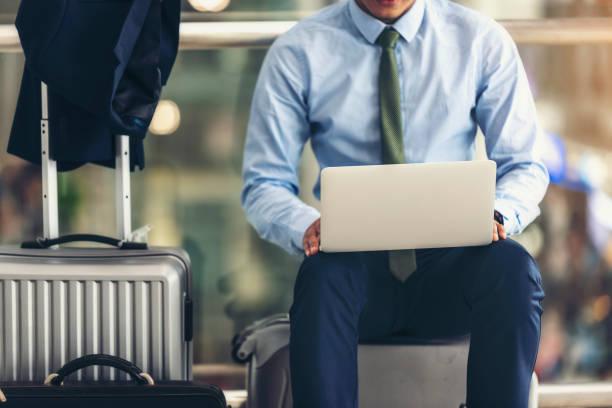 Asiatische Geschäftsleute sind Laptop verwenden, um ihre Flüge zu den airport.focus auf Laptop zu überprüfen. – Foto