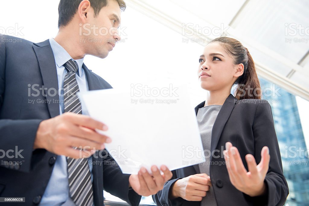 Asian businesswoman and businessman standing and discussing document royalty-free stock photo