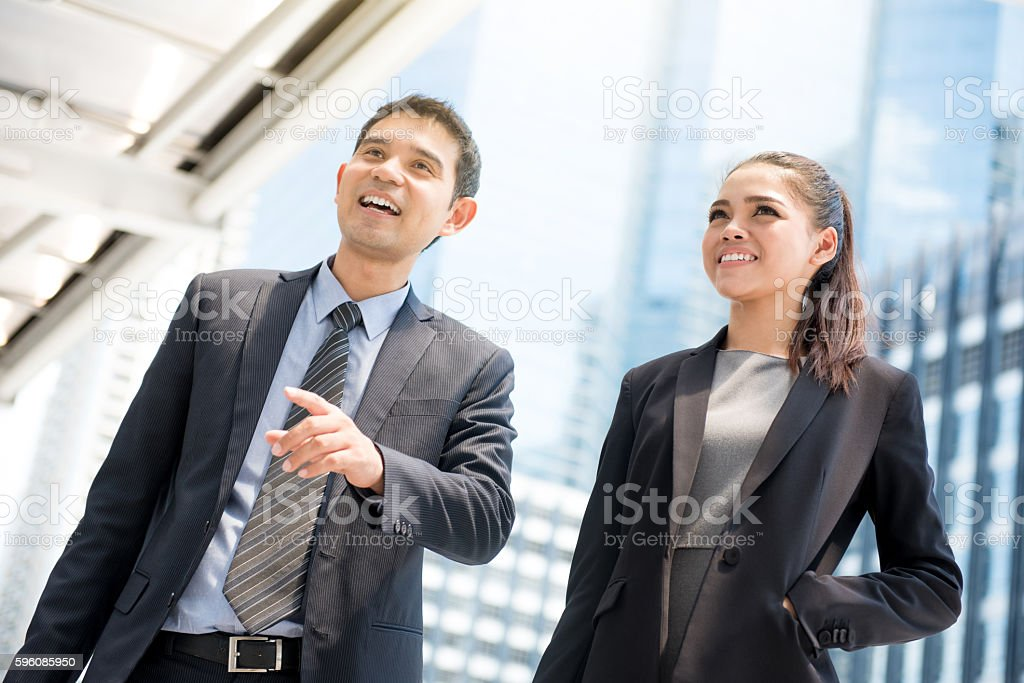 Asian businesswoman and businessman standing and talking outdoor royalty-free stock photo