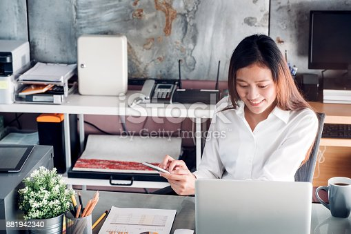 836871418 istock photo Asian businesswoman chattin on mobile phone in front of laptop computer at office,Office lifestyle concep 881942340