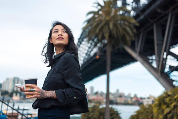 asiatische geschäftsfrau, trinken kaffee und mit smartphone - kaffeetasse tattoo stock-fotos und bilder