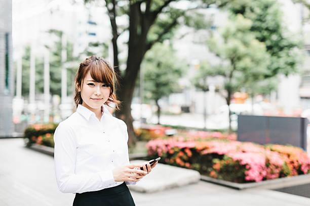 Asian Businesswoman Holding a Phone with a Smile ストックフォト