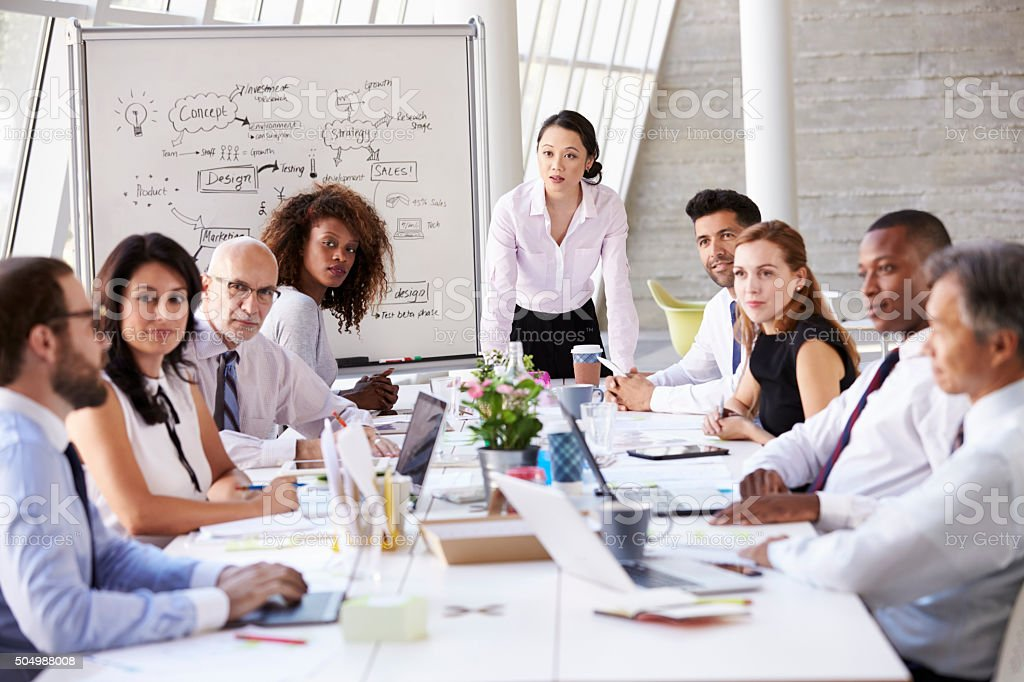 Asian Businesswoman Leading Meeting At Boardroom Table stock photo