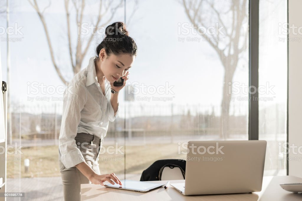 Asian businesswoman on the phone and using digital tablet stock photo