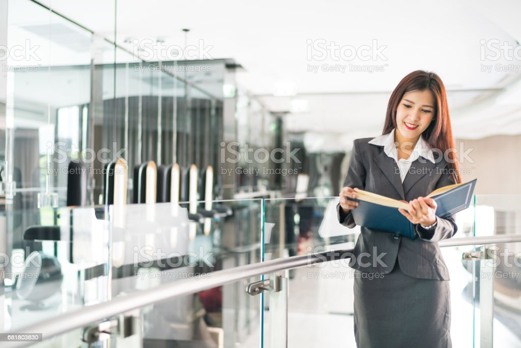 Asian businesswoman or college teacher reading textbook in modern office, business or education concept stock photo