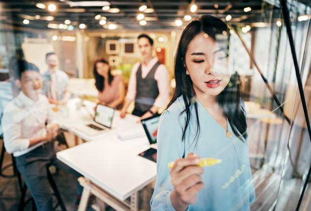 亞洲女商人介紹她對公司發展的想法 - 亞洲 個照片及圖片檔