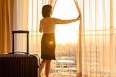 Rear view of Japanese businesswoman in the hotel room pulling the curtains to see the view