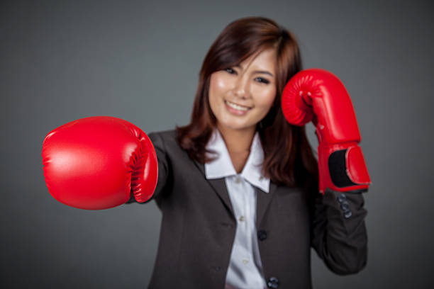 Asian businesswoman punch with boxing glove focus at the glove stock photo