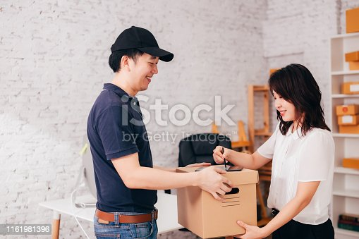 istock Asian businesswoman receiving parcel from courier 1161981396