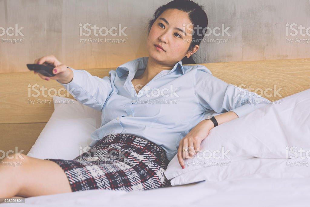 asian businesswoman resting in the hotel room, watching tv and...