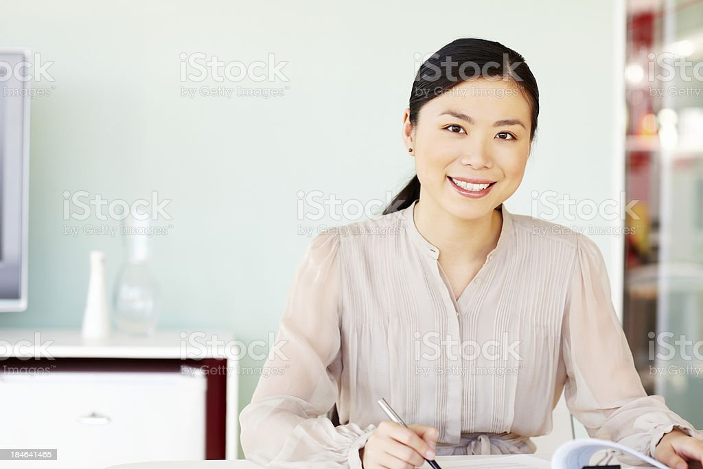 Asian Businesswoman Sitting at Her Desk stock photo
