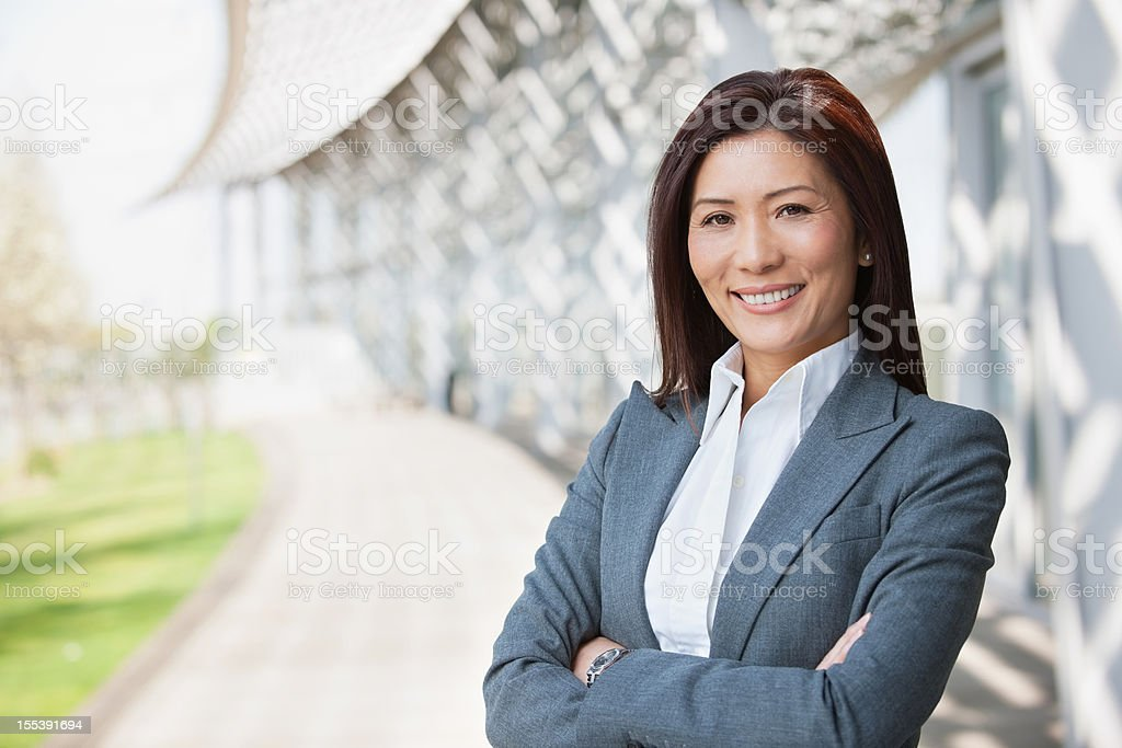 Asian Businesswoman Smiling With Arms Crossed stock photo