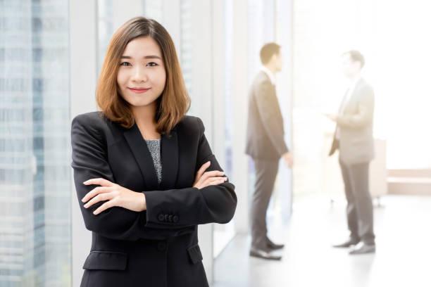 Asiatische Geschäftsfrau steht und überquert ihre Arme im Bürogebäude Flur – Foto