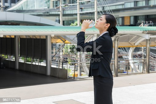 Asian businesswoman standing and drinking pure mineral water from plastic bottle with background of building.