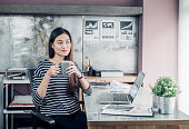 Asian businesswoman take a coffee break after working with smiling face,Happy office life concept,working woman at modern home office.