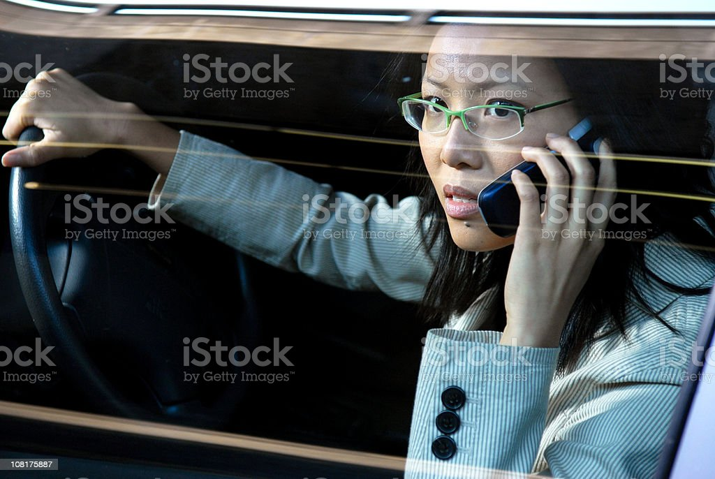 Asian Businesswoman Talking on Cell Phone While Driving Car royalty-free stock photo