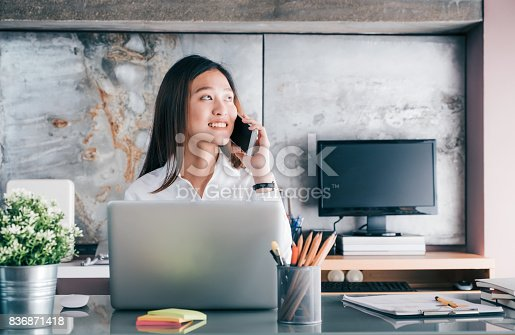 istock Asian businesswoman talking on mobile phone in front of laptop computer and looking out of window at office,Office lifestyle concept. 836871418