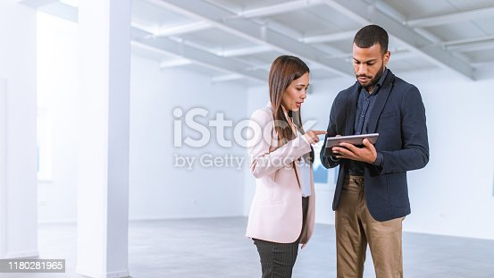 Asian businesswoman asking an African-American interior designer holding a digital tablet question on furnishing the empty office they are standing in while he is showing her options on a digital tablet.