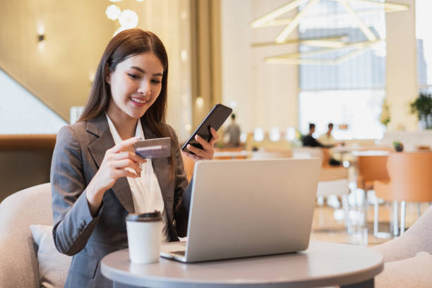Asian businesswoman using credit card and mobile phone for online financial payment and shopping stock photo
