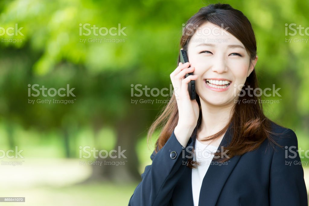 asian businesswoman using smart phone in park stock photo