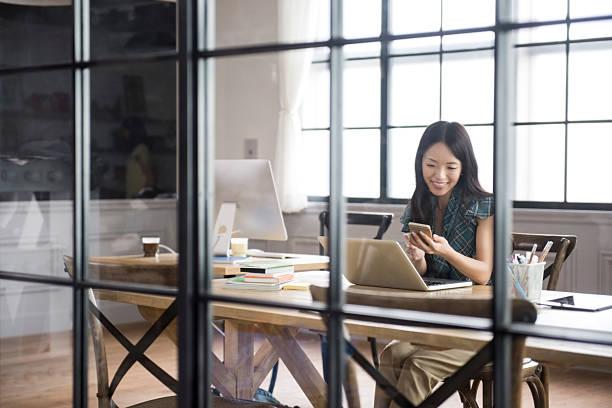 asian businesswoman using smartphone - 虛擬辦公室 個照片及圖片檔
