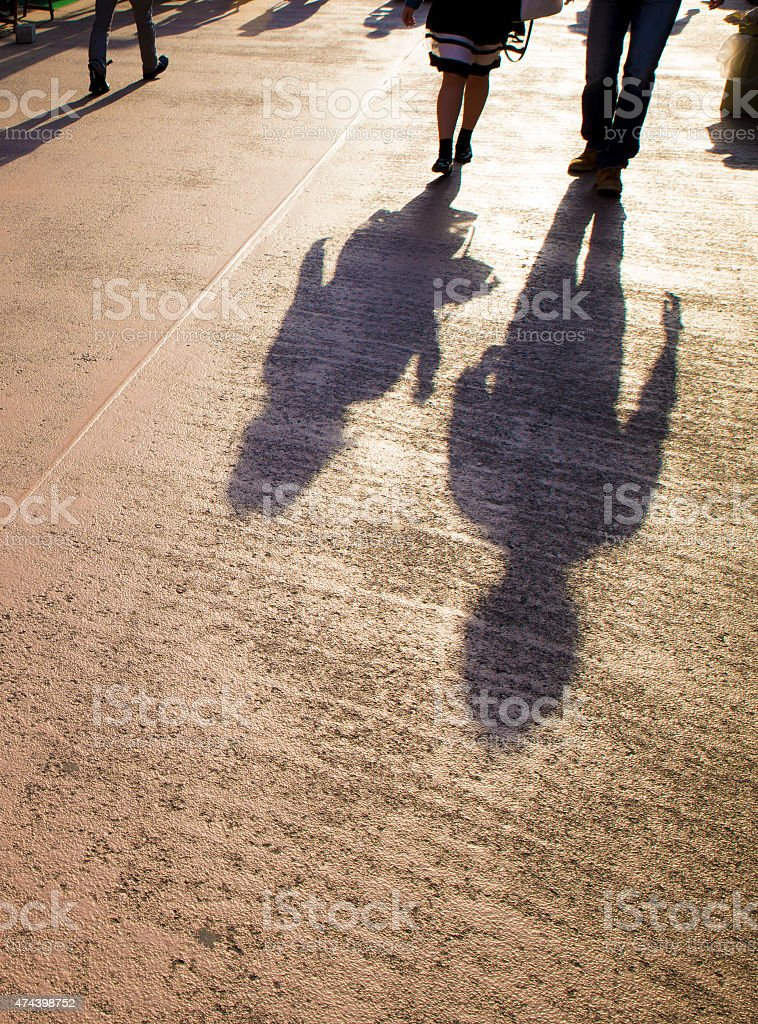 Asian businesswoman walking in street with long shadows stock photo
