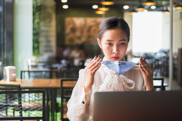 Asian businesswoman wearing protective face mask while working with laptop to protect pollution from dust PM2.5 and coronavirus covid-19 stock photo
