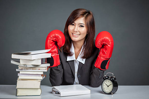 Asian businesswoman with boxing glove ,books and clock stock photo
