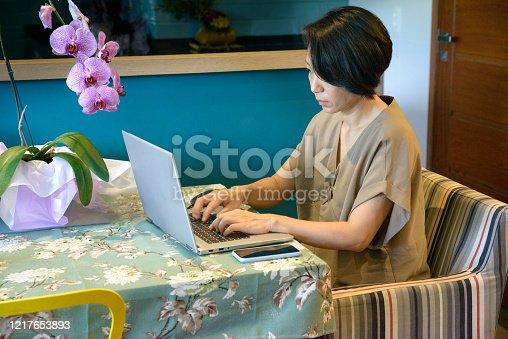 Asian woman sitting typing on laptop profile view
