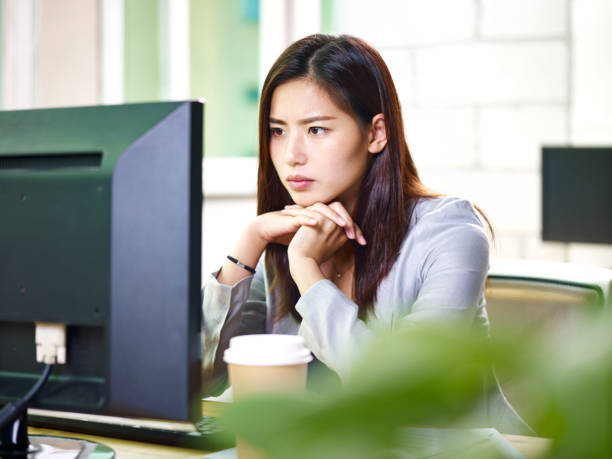 asian businesswoman working in office - frowning stock photos and pictures