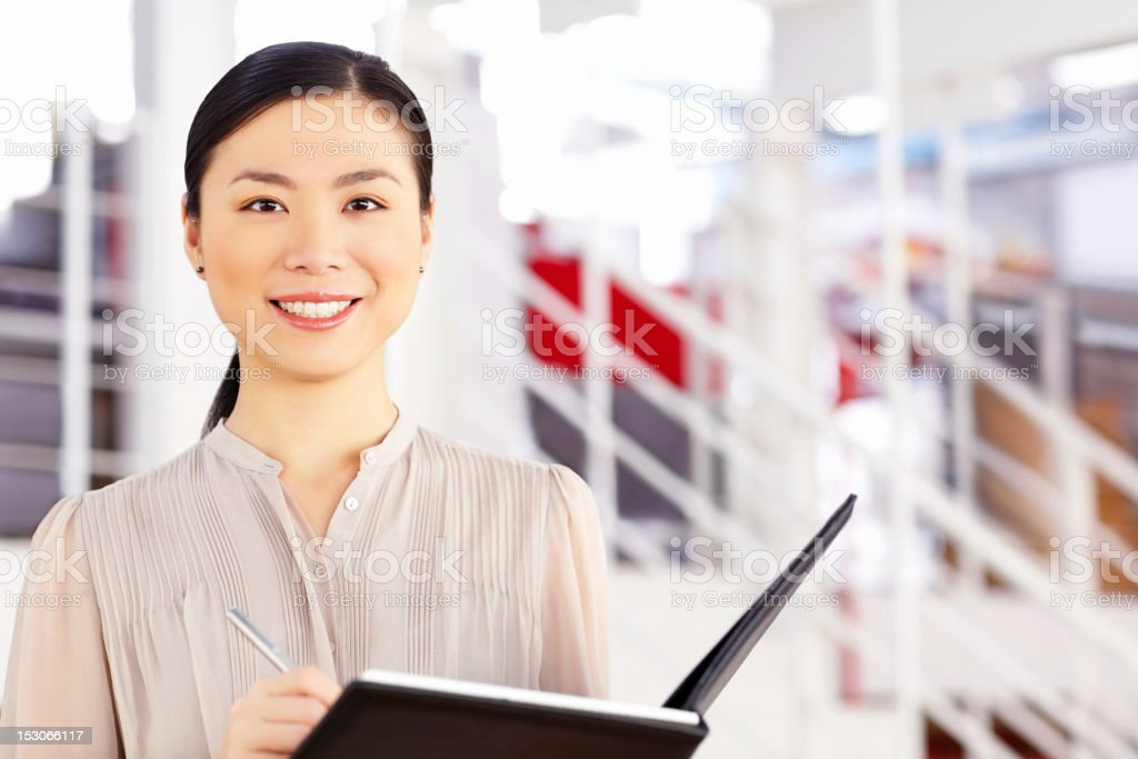 Asian Businesswoman Writing in a Binder royalty-free stock photo