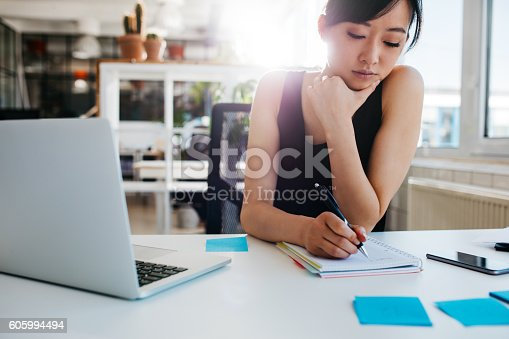 Shot of asian businesswoman writing notes on notepad. Female executive sitting at her desk with laptop taking notes.