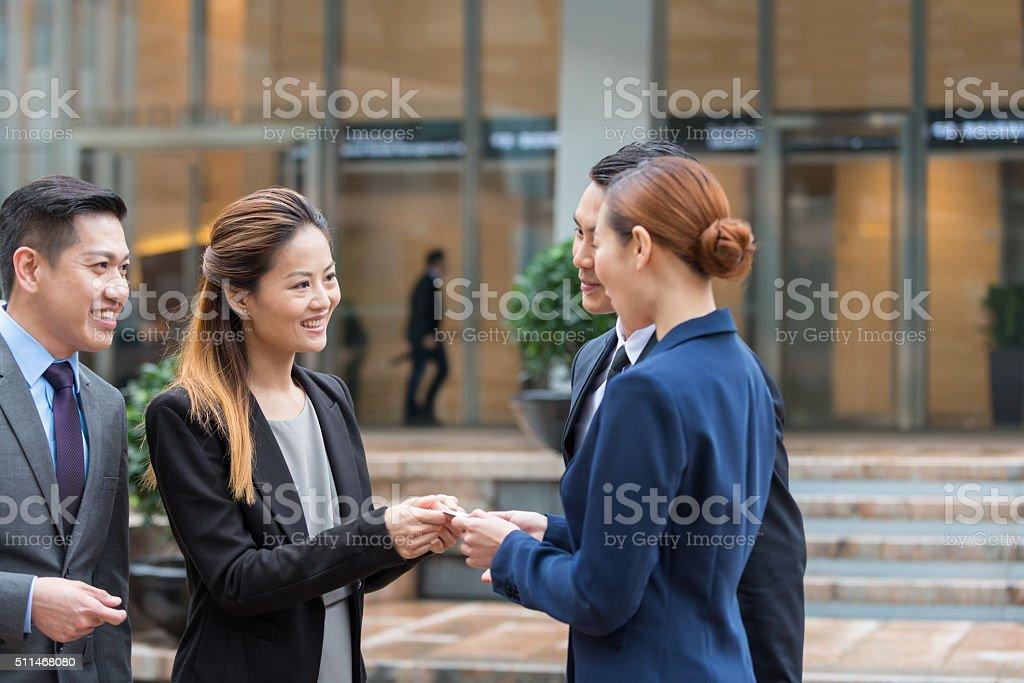 Asia mujeres de negocio y ejecutivos intercambiando tarjetas de visita, Hong Kong, China - foto de stock